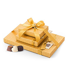 Three gift boxes from Godiva's Gold Discovery collection are tied together with a luxurious gold ribbon and presented in a stylish gold bag.