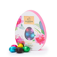 An ornate egg shaped gift box is filled with an assorted selection of individually wrapped Godiva chocolate Easter eggs.