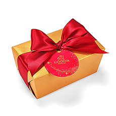 The timeless Godiva Gold Ballotin is all dressed up for the holidays with a satin ribbon and a tag shaped like an ornament. Untie the rich red ribbon and unwrap the shimmering gold paper to reveal this exciting gift ballotin filled to the brim with the very best Godiva chocolates.